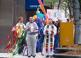 Group with rainbow stoles, banners, water approach