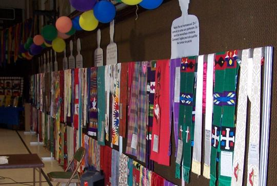 Colorful stoles hanging along a wall.